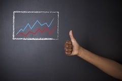 South African or African American teacher or student thumbs up against blackboard chalk growth line graph Royalty Free Stock Images