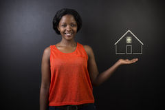South African or African American woman teacher or saleswoman against black background with home house or real estate Royalty Free Stock Photography