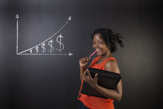 South African or African American woman teacher or student against blackboard background money graph. South African or African American woman teacher or student Stock Image