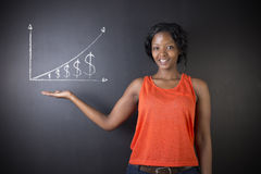 South African or African American woman teacher or student against blackboard chalk money graph. South African or African American woman teacher or student hand Stock Photos