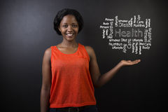 South African or African American woman teacher or student against blackboard health diagram Stock Image