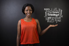 South African or African American woman teacher or student against blackboard strategy diagram Royalty Free Stock Images