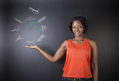 South African or African American woman teacher or student with chalk globe and jet world travel Royalty Free Stock Photography