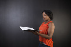 South African or African American woman teacher or student with diary notepad Stock Photo