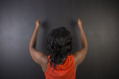South African or African American woman teacher or student fists up on blackboard Stock Photography