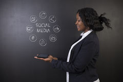 South African or African American woman teacher or student holding tablet social media Stock Images