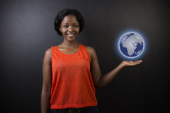 South African or African American woman teacher or student holding world earth globe. In the palm of her had on black background Stock Photos