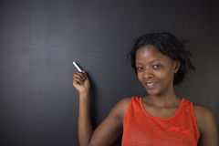 South African or African American woman teacher or student holds points chalk on blackboard Stock Photo