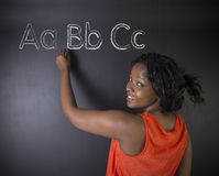 South African or African American woman teacher or student learn alphabet write writing. On chalk blackboard background Royalty Free Stock Image