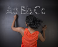 South African or African American woman teacher or student learn alphabet write writing. On chalk blackboard background Royalty Free Stock Photography