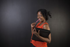 South African or African American woman teacher or student with notepad and pen Stock Images