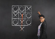 South African or African American woman teacher writing tic tac toe on chalk black board background Royalty Free Stock Photos