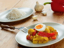 South African curry with vegetables, fruit and eggs. Traditional South African curry dish (vegetarian) with dried apple, pepper, raisins and eggs and served with Royalty Free Stock Images
