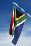 South African Flag. With clipping path, hanging from flagpole against blue sky royalty free illustration
