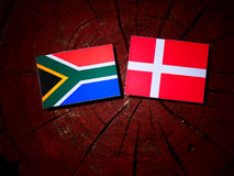 South African flag with Danish flag on a tree stump isolated. South African flag with Danish flag on a tree stump stock photo