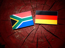 South African flag with German flag on a tree stump royalty free stock image