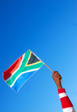 South African flag in hand stock photography