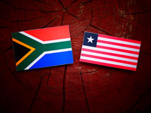 South African flag with Liberian flag on a tree stump isolated. South African flag with Liberian flag on a tree stump stock photo