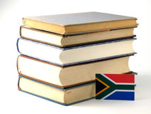 South African flag with pile of books isolated on white backgrou royalty free stock photo