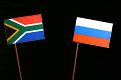 South African flag with Russian flag isolated on black. Background stock photo