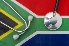 South African flag and stethoscope. The concept of medicine. Stethoscope on the flag in the background stock photography