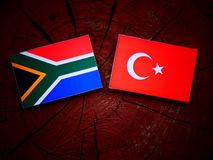 South African flag with Turkish flag on a tree stump royalty free stock image