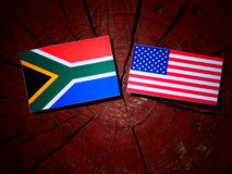 South African flag with USA flag on a tree stump stock image