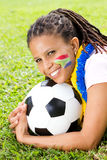 South african football fan. Young female south african football fan lying on green grass with south african flag painted on her face royalty free stock image