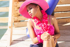 South african girl is wearing pink hat near sea Royalty Free Stock Photos