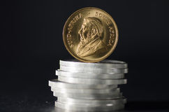 South African Gold Coin Krugurand on Silver Coins. On black background Stock Images