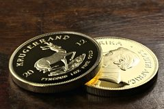 South African gold bullion coins. South African 1 ounce gold bullion coins on wooden background Royalty Free Stock Photo