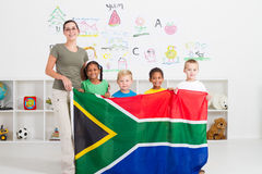 South african preschool. A happy south african preschool students and teacher holding the SA flag in the classrom royalty free stock image