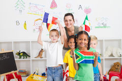 South african preschooler. A happy young south african preschooler holding flag with classmates and teacher holding diverse flags in background royalty free stock photography
