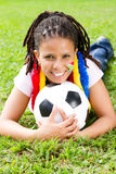 South african soccer fan. Young female south african soccer fan lying on green grass with south african flag painted on her face stock photos