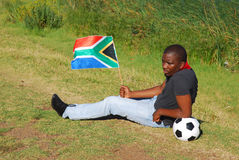 South African soccer fan sad. A young black male soccer world cup fan with South African flag and football lying in the grass with sad and disappointed Royalty Free Stock Photo