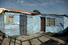 South African township. Wooden shack with blue peeling paint in a South African township near Cape Town stock photography