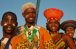 South African traditional people. A dance group of four black South African people dressed in colorful traditional clothes with happy smiling facial expression