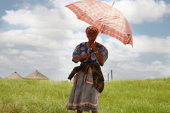 South African woman holding an umbrella  to protect her from the Royalty Free Stock Image
