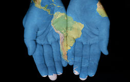 South America In Our Hands. Map painted on hands showing concept of having South America in our hands Stock Photo