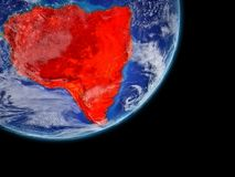 South America in red on Earth from space. South America on realistic model of planet Earth with very detailed planet surface and clouds. Continent highlighted in stock illustration