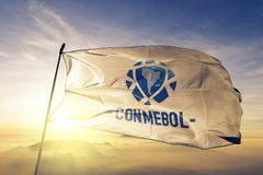 South American Football Confederation CONMEBOL flag textile cloth fabric waving on the top sunrise mist fog. Beautiful stock photo