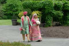 South Asian Couple in Wedding Attire. A newly wedded South Asian man and a woman wearing colorful traditional wedding attire of their culture are taking a stroll Stock Photos