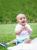 South Asian Indian baby boy in park on ground. Portrait of cute adorable little indian South Asian infant boy in white shirt sitting on ground with toys in park Royalty Free Stock Photo