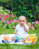 South Asian Indian baby boy in park on ground. Portrait of cute adorable little indian South Asian infant boy in white shirt sitting on ground with toys in park Stock Photo