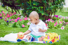 South Asian Indian baby boy in park on ground. Portrait of cute adorable little indian South Asian infant boy in white shirt sitting on ground with toys in park Stock Photos