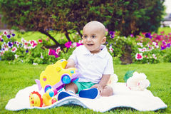 South Asian Indian baby boy in park on ground. Portrait of cute adorable little indian South Asian infant boy in white shirt sitting on ground with toys in park Royalty Free Stock Photography