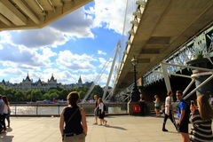 South Bank River Thames London. People relaxing on Thames River South Bank by Hungerford Bridge and Golden Jubilee Bridges on summer Sunday, London United Royalty Free Stock Photography