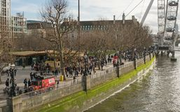 The South Bank of River Thames at Westminster, London, England. Crowds of people on the South Bank of the River Thames at Westminster by the London Eye, London royalty free stock images