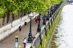 South Bank. The walkway on the south bank of the river Thames in London, England, with people walking and jogging along the river stock photos