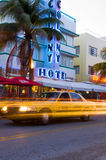 South beach miami art deco hotels. SOUTH BEACH, MIAMI-APRIL 19: Taxi cab on Ocean Drive in motion   in front of art deco hotels in South Beach, Miami, Florida Royalty Free Stock Photography